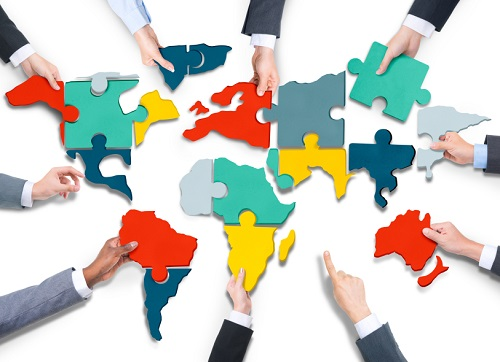 Diverse Business People's Hands with Cartography Puzzle